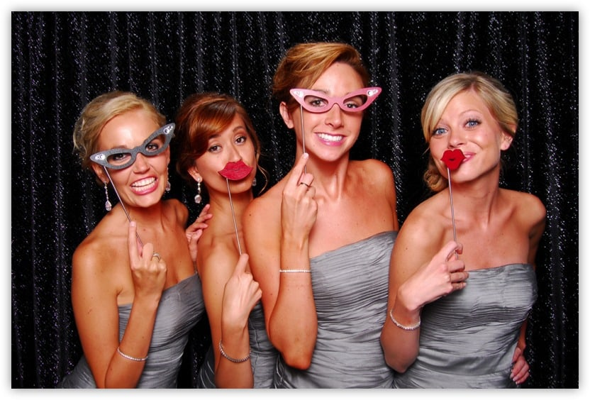 four bridesmaids striking a pose with props on a stick