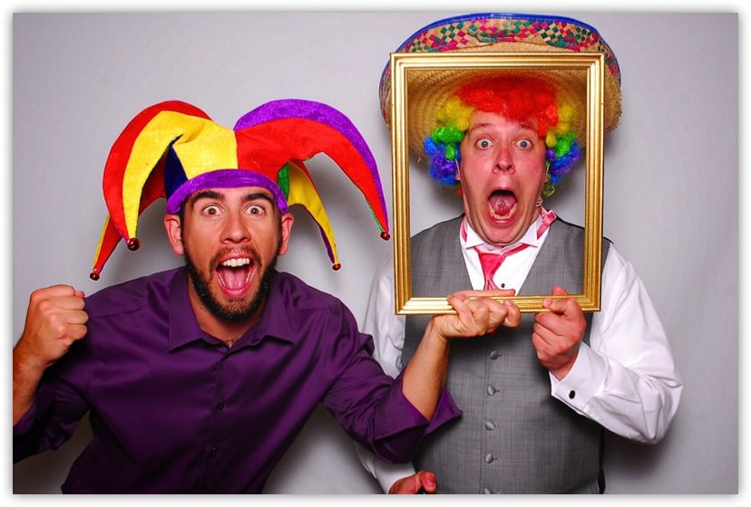 Two men clowning around in a photo booth