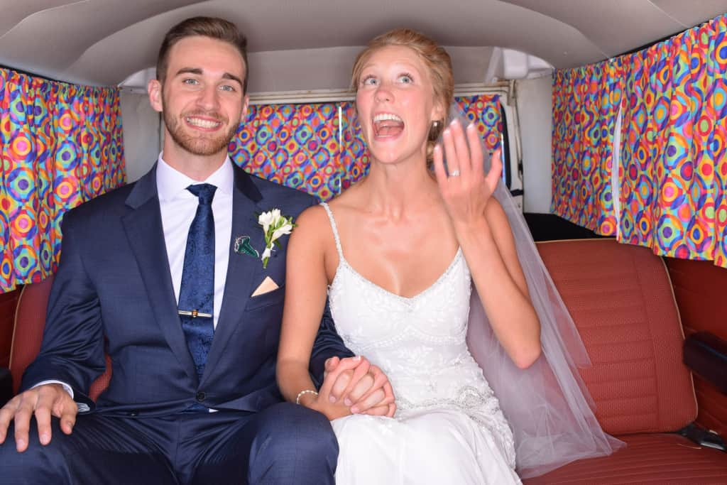 Recently married couple in the back of a volkswagon van
