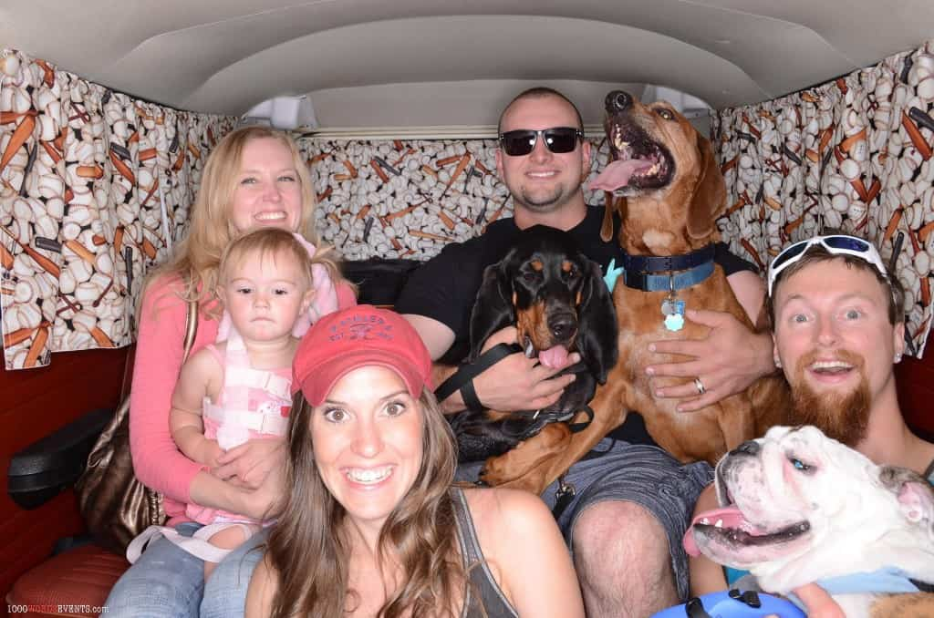 A family sitting in a volkswagen van with three dogs