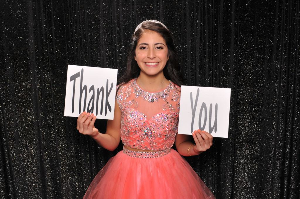 young girl at a Quinceañera holding a thank you sign
