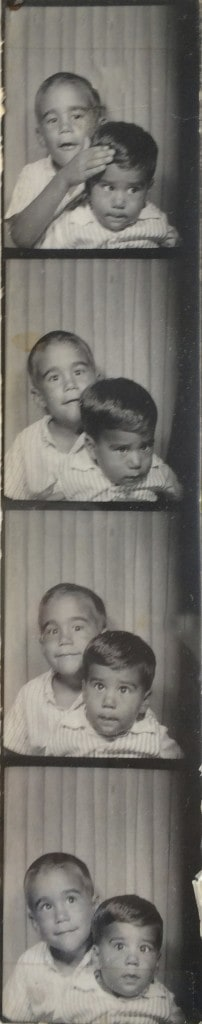 two boys posing in an old time photo booth  photo strip