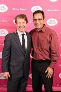 Martin Short and Michael Abella posing in front of a step and repeat background