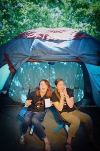 two women acting scared in a tent
