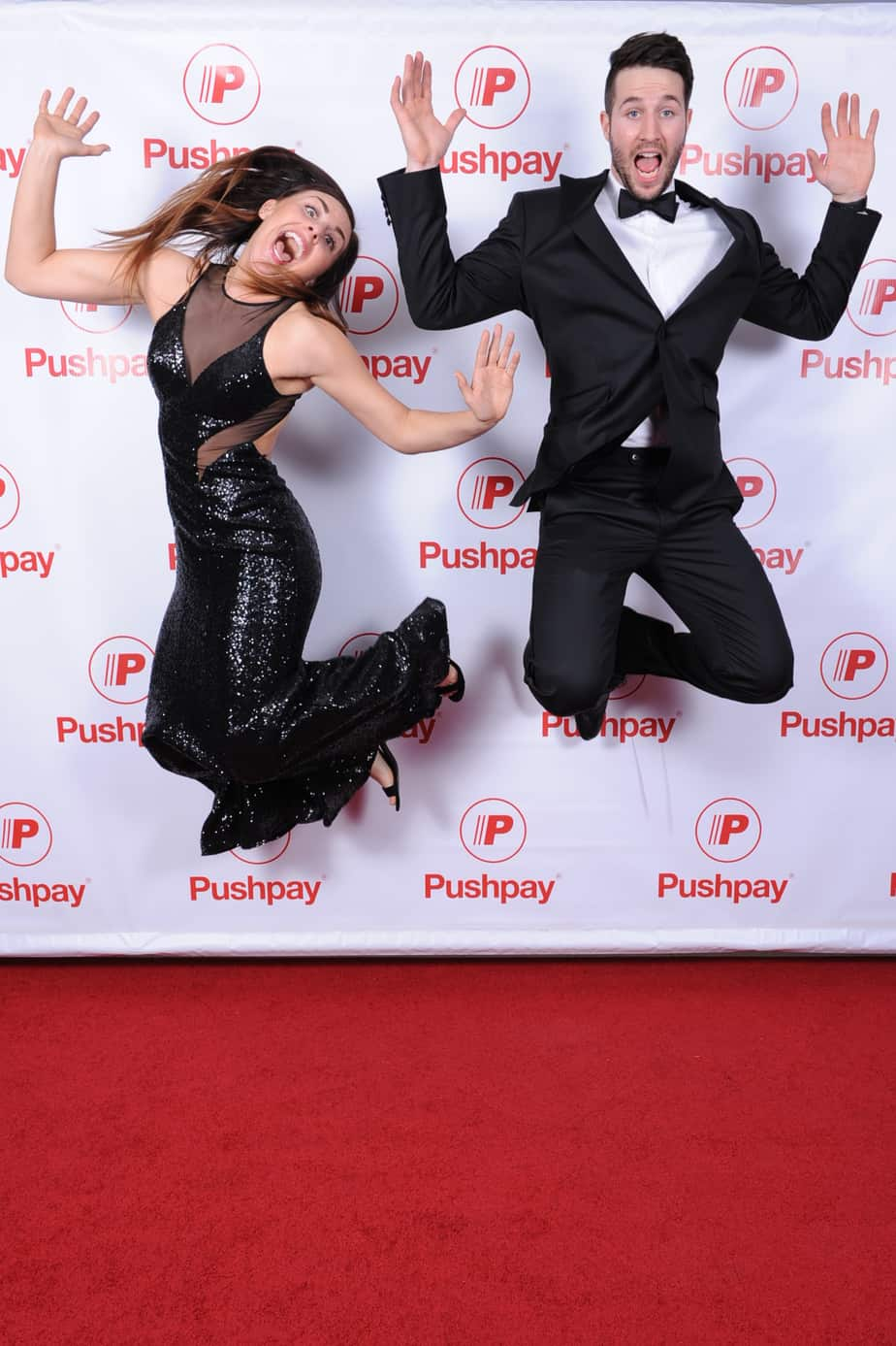 two peole jumping on the red carpet