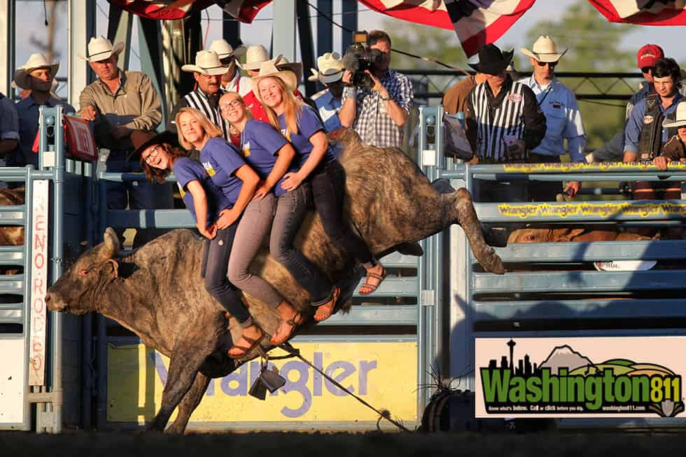 Four Women riding bucking bull at rodeo produced using green screen photography