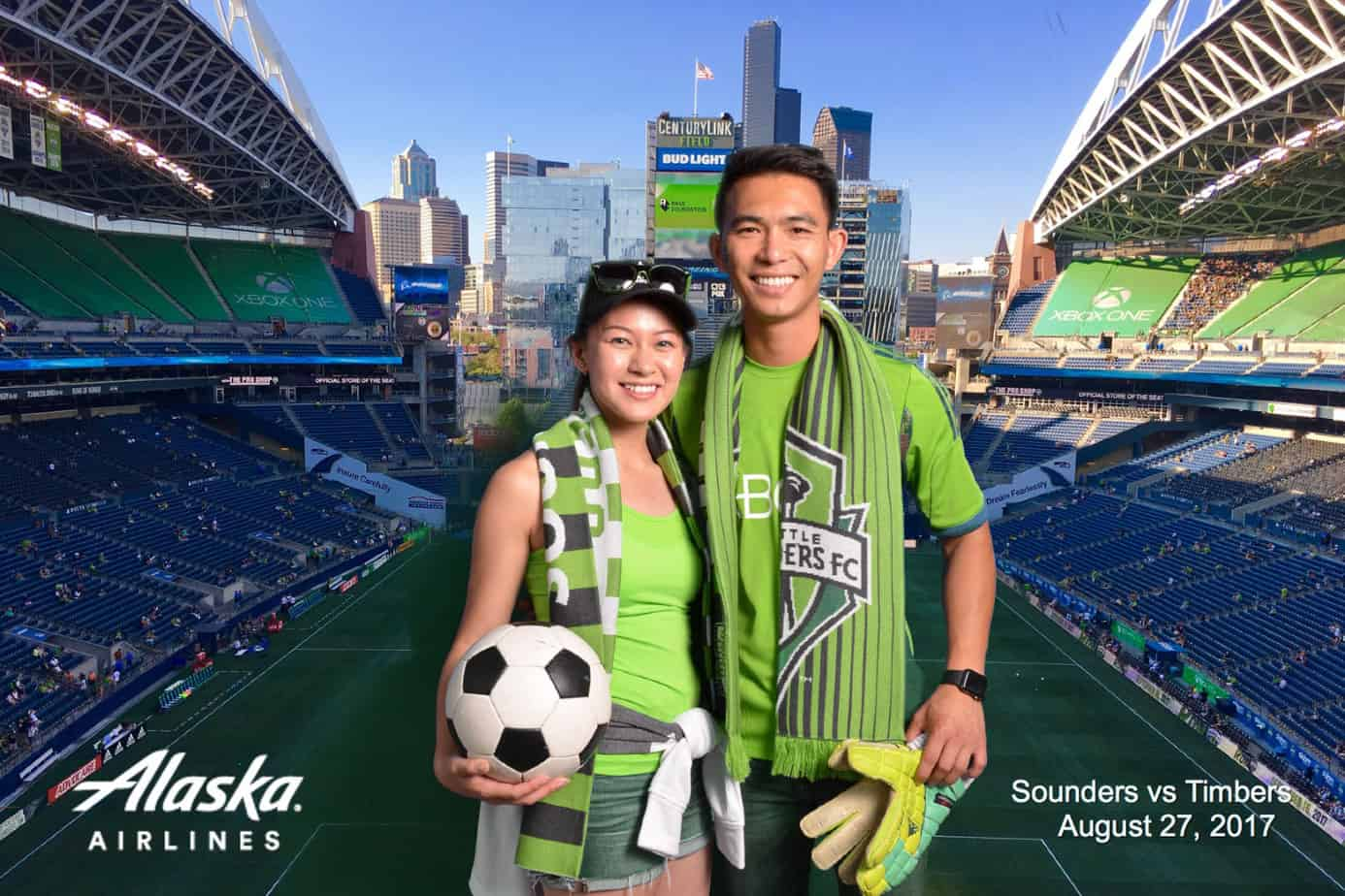 Man and a Women posing at Century Link field in Seattle during a soccer match.