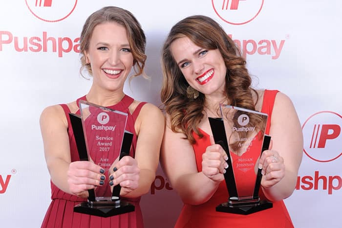 Two women holding up their awards in front of a step and repeat background