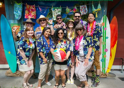 Men and Women posing at a Hawaiin themed company picnic